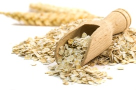 Oatmeal flakes with wooden scoop on white background